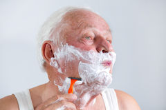 Senior man shaving his beard Royalty Free Stock Photos