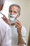 Senior man shaving at home, using razor and shaving foam, reflection in bathroom mirror, smiling, rear view, portrait (differentia Royalty Free Stock Images
