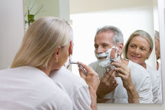 Senior man shaving at home, woman embracing man, watching, reflection in bathroom mirror, rear view royalty free stock photography