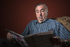 Senior man shocked with news. Older retired man surprised negatively with what he's reading in the newspaper Royalty Free Stock Photo