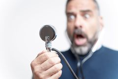 Bad blood pressure results for a senior man. Senior man shocked and outraged with his blood pressure measurement result, studio image Royalty Free Stock Photos