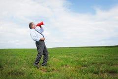 Senior man shooting. Senior business man shooting through a red megaphone ina meadow Royalty Free Stock Photography