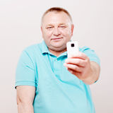 Senior man shooting on smartphone over white. Middle aged man in blue shirt taking picture on his mobile phone over white background Stock Photo