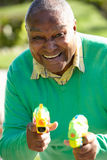 Senior Man Shooting Water Pistols Royalty Free Stock Photos