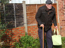 Senior man with a shopping bag. A senior man with a walking stick and a shopping bag Stock Photography