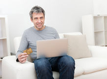 Senior man shopping at home using laptop Stock Images