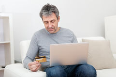 Senior man shopping at home using laptop Stock Image
