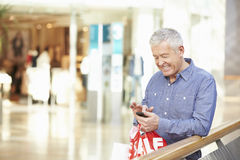 Senior Man In Shopping Mall Using Mobile Phone Royalty Free Stock Images