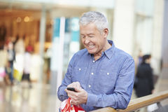 Senior Man In Shopping Mall Using Mobile Phone Stock Photography