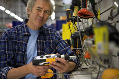Senior man shopping for power drill in DIY shop, smiling, portrait Royalty Free Stock Photos