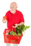 Senior Man Shops for Produce. Healthy senior man shopping for organic produce and holding out a tomato.  Isolated Royalty Free Stock Photography
