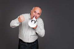 Senior man shouting with megaphone. Emotional senior man shouting with megaphone against grey background Royalty Free Stock Photos