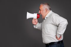 Senior man shouting through the megaphone. Studio shot over grey background Stock Images