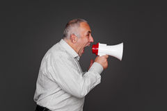 Senior man shouting using megaphone. Sideview of senior man shouting using megaphone over grey background Royalty Free Stock Photo