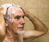 Senior man in shower. Senior man washing hair in the shower Stock Photo