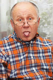 Senior man showing his tongue. Casual bald senior man emotional portrait series. Sticking out the tongue Royalty Free Stock Image