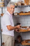 Senior Man Showing Muffins In Supermarket Stock Photo
