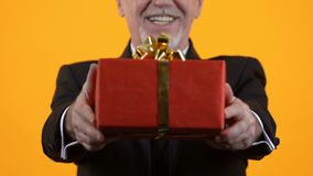 Senior man showing red gift box, birthday present, holiday surprise, affection. Stock footage stock footage