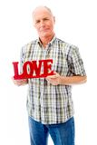 Senior man showing a red Love text. Senior man in his 60's shot in studio isolated on a white background Stock Photo