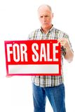 Senior man showing a for sale sign Royalty Free Stock Photos