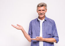 Senior man. Is showing something, standing on white background royalty free stock photos