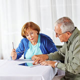 Senior man showing woman tablet Royalty Free Stock Photo