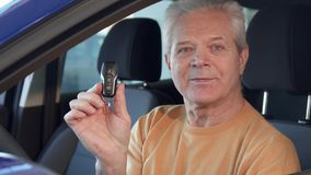 Senior man shows car key through the window. Attractive senior man showing car key though the window. Gray male customer sticking his hand out of the vehicle Stock Photography