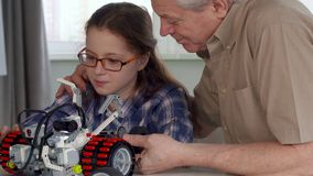 Senior man shows his granddaughter something on toy vehicle stock images
