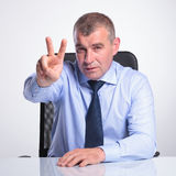 Senior man shows victory from desk Royalty Free Stock Image