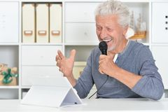 Senior man singing karaoke with tablet. Emotional senior man singing karaoke with tablet at home Royalty Free Stock Photo