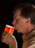 Senior man sipping from pint glass beer. Senior caucasian man in profile drinking from a pint glass of beer or lager stock image