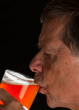 Senior man sipping from pint glass beer. Senior caucasian man in profile drinking from a pint glass of beer or lager stock photos