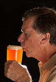 Senior man sipping from pint glass beer. Senior caucasian man in profile drinking from a pint glass of beer or lager stock photo