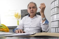 Senior man with sits at a desk, scrolling in a document file Royalty Free Stock Photography