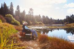 Senior man sits fishing, Bluff Lake, Big Bear, California Royalty Free Stock Photos