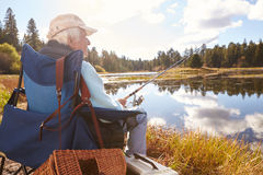 Senior man sits fishing in a lake, back view close-up stock photos