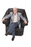 Senior man sitting. Image of a senior man sitting in an armchair against a white background Royalty Free Stock Images