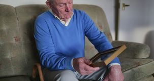 Bringing Back Memories. Senior man is sitting alone in the living room of his home, looking at an old photo stock footage