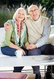 Senior Man Sitting With Arm Around Woman On Couch Stock Photography
