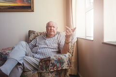 Senior man sitting at assisted living facility. Indoor shot of a caucasian senior man sitting at assisted living facility. Elderly man sitting on an arm chair by stock photo