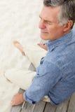Senior man sitting by beach Stock Photos