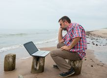 Senior man sitting at the beach with laptop Royalty Free Stock Photo