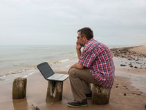 Senior man sitting at the beach with laptop Stock Image
