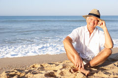 Senior man sitting on beach relaxing Royalty Free Stock Images