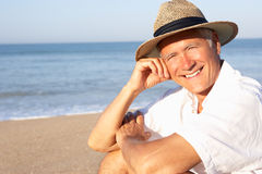 Senior man sitting on beach relaxing Stock Images