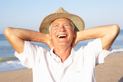 Senior man sitting on beach relaxing Royalty Free Stock Image