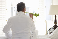 Senior man sitting on bed holding celery stick, rear view Royalty Free Stock Photos
