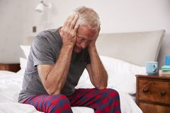 Senior Man Sitting On Bed At Home Suffering From Depression royalty free stock photos