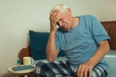Senior Man Sitting On Bed Suffering From Depression royalty free stock photography