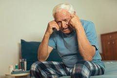 Senior Man Sitting On Bed Suffering From Depression. Senior Man Sitting On Bed At Home Suffering From Depression Royalty Free Stock Photo